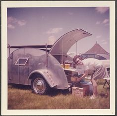 1960s teardrop travel trailer picnic barbecue camper silver with young woman camp campy odd