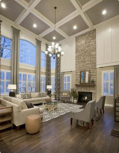 Great room. Large picture windows. Window wall. Custom curtain panels. Chandelier. Stone fireplace. Raw wood mantle. White trim moldings. Grey ceiling.