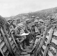 WWI, 28 Feb 1918; Officers of 1/7th Battalion, King's Liverpool Regiment checking a map in trenches on the La Bassee Canal sector. Cropped. © IWM (Q 10740)