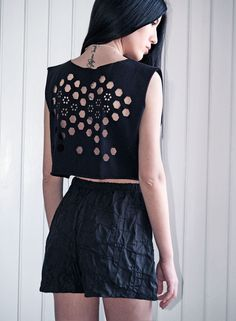 $24 A laser cut womens top in black color by Dionisis Chalikias for muchö.  I wanted somehow to add more dimension to the fabric  by creating a new type of lace on t-shirts and tops for this summer, Dionisis says.  After discovering the potential of using laser cutting technology on making jewelry,  we wanted to experiment even more on fabric.  So, I started to create simple 80s inspired patterns of sleeveless tees and lose fit tops.  Then I created motifs, shapes, skulls and abstract forms…