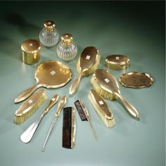 A fifteen-karat gold and diamond dressing set, London import marks for Stuart Dawson & Co. Ltd., 1914-15, the small tray with import marks for 1921-22, otherwise apparently unmarked with diamond-set monogram EDB, comprising: two hand brushes, a hand mirror, two clothes brushes, two combs, two gold-mounted glass bottles, a shaped oval box with hinged cover, a circular box with detachable cover, a gold and silver-plated shoe horn, a gold and silver-plated button hook,