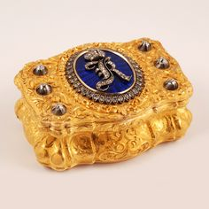 A magnificent continental, probably German, gold, diamond and enamel presentation snuff box. Of cartouche form, decorated with elaborate cast and chased scroll and floral motifs, diamond set imperial cipher of Grand Duke Konstantin Nicholaevich, against a field of cobalt blue translucent enamel over a sunburst, engine turned ground.