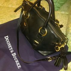 Dooney & Bourke Top Handle Satchel Black leather, brass hardware, signature red interior, brass feet, stylish side tassels, removable shoulder strap Dooney & Bourke Bags Satchels