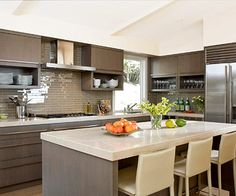 L-shaped kitchen w/island: A benefit of an L-shaped kitchen is the ability to center a table in the space. This puts the family close to where the meals are prepared and draws guests near the cook when the homeowners are entertaining. The appliances are along the back wall and the refrigerator is on the side wall, which creates a large work triangle.