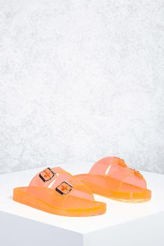 b314a4c8d8e A pair of clear jelly sandals featuring a dual strap design with buckle  accents