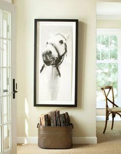 A reproduction of an old horse photo, from the Los Angeles store Natural Curiosities, hangs above a bucket of firewood in the family room.