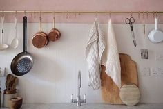 pink kitchen with gold bar and hooks hanging pots