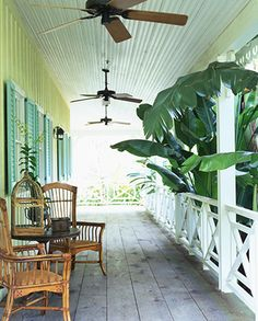 Vernacular wooden house & porch with rattan chairs, ceiling fans, & lush vegetation.