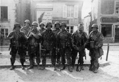 """By morning, in the square of Sainte-Marie-du-Mont, paratroopers of """"Easy"""" Co. 506th PIR, 101st Airborne Division, F. Guth, F. Mellet, D. Morris, D. West, F. Talbert and C.T. Smith, pose with 3 GIs at 4th ID (behind) that came from Utah Beach. 7 June 1944."""