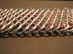 Dragon scale chainmail armband, van kleinere ringetjes, multi colour binnenkant. FB: Tessa's chainmail workshops
