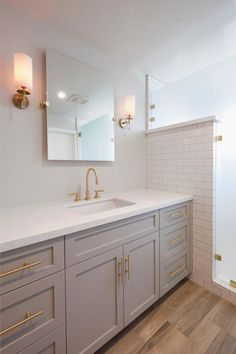 Ample counter space and storage allow for maximum functionality, while the materials and finishes highlight the crisp fresh ambiance of this master bathroom. A large walk-in shower sits adjacent to the vanity and acts as a spa-like escape for the homeowners.