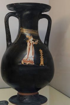 Double Aulos Player. Female figure to right, with long curls, back hair tied in a bunch, earrings, necklace, long sleeved white chiton with red borders and stripes, and shoes; she plays the double flute, and before her is an incense-burner.  Black glaze Gnathian pelike. Height 35.6 cm; diameter 21 cm. Attributed to The Naples Harp Group. Ca. 330 BC. From Gela, Sicily. London, The British Museum  - Vase # F557.