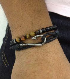 Kit unissex com 2 pulseiras sendo: - 1 pulseira com couro trançado na cor preto, com 2 voltas no punho e fecho com anzol em banho grafite. - 1 pulseira de pedra ônix contendo detalhe com pedra olho de tigre.