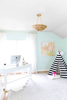 Feminine workspace with a gold chandelier and a play area for kids