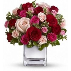 The stylish bouquet features large red and pink roses accented with smaller spray roses in shades of red and pinks. Delicate green oregonia and pittosporum add a fresh contrast, and all comes arranged and delivered in our exclusive Mirrored Silver Cube vase.