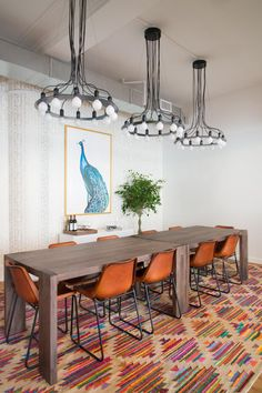 A bright, multicolor rug is complemented by burnt orange chairs and a large blue and white painting in this contemporary conference room. A trio of industrial-style chandeliers with exposed light bulbs hang above a sleek, wood conference table adding a funky flair.