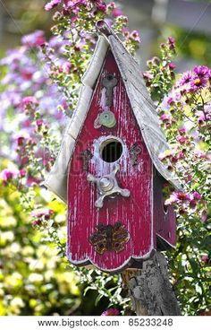 Old purple wooden bird house in garden