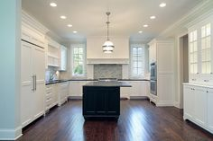 Stunning open kitchen design with white Shaker style cabinetry and black center…