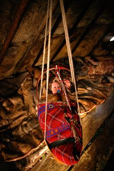 A Nenets baby hanging in a cradle in a reindeer skin tent. Yamal, Siberia, Russia