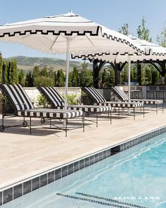 Patio features a row of black and white striped pool loungers accented with black and white canopies facing the in ground pool.