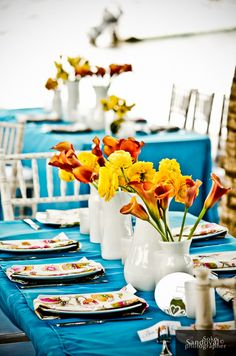 White glass centerpieces with orange and yellow flowers on turquoise blue chiffon