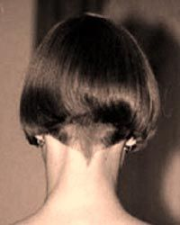 "The shingle or the ""boyish bob"" introduced in 1923 featured hair which tapered into a V-shape at the nape of the neck with either waves or spit curls at the sides."