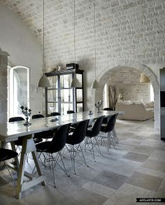 black Eames chairs surrounding a long table in a white dining room with white pendant lights, a long table and painted brick wall with arched entryway into a living room Interior Design Minimalist, Minimalist Decor, Home Interior Design, Interior Architecture, Minimalist Bedroom, Brick Interior, Minimalist Kitchen, Minimalist Living, Installation Architecture