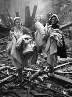 WWII: The morning after a direct hit by a high explosive bomb on St. Matthew's Hospital, Shoreditch, in London, on Oct. 9, 1940. In spite of the night's experiences nurses are on the job rescuing blankets and other bedding from among the debris.