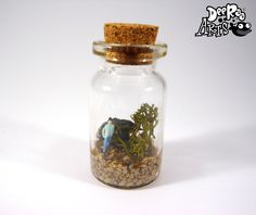 """Quirky, cute mini world in a bottle. This one features Glenn, a slightly confused little man just getting used to his new surroundings. He will come round eventually though. This bottle will come on a 20"""" Silver Plated Snake Chain NecklaceThis bottle is 2 1/2cm tall Not suitable for Children, this bottle is made of glass and must be handled with care."""