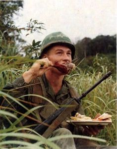 A member of the Air Cav Div eats a turkey drumstick while having Thanksgiving in the field. 10 Nov 1967.