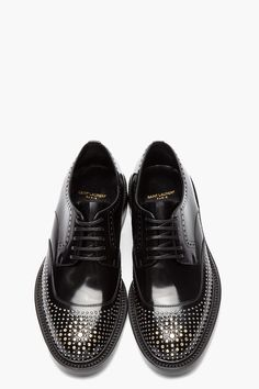 SAINT LAURENT // Black and silver nail-perforated brogues 32418M049001 Low-top patent leather brogues in black. Almond toe. Tonal Derby-style lace-up closure. Metallic studding throughout toe cap and sides in tones of silver and gold. Brogue-style perforations along lace tabs and throat. Black leather sole. Tonal stitching. 100% leather. Made in Italy. $980 CAD
