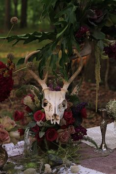 """A photo shoot, under the New Orleans oak trees. An arrangement with, a dusty rose """"Amnesia"""", white veronica, purple stock, hot pink garden roses, purple cabbage, green hanging amaranthus, lotus pods, scabiosa pods, dusty miller, philodendron leaves and sarracenia (pitcher plants). Touches of antique silver pieces and an animal skull make this wedding banquet arrangement very rustic but elegant at the same time. *Phew!* Did I forget anything?!"""