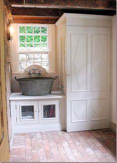 Galvanised tub sink, brick tile flooring, rustic timber beams and panelled storage doors...stunning!