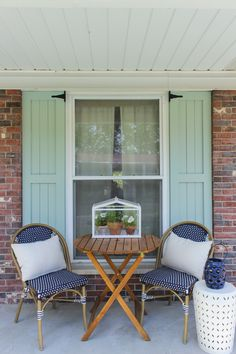 Aqua Craftsman shutters with navy bistro set on front porch