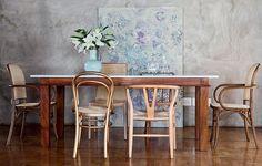 O cimento queimado das paredes ganhou a companhia do grande quadro, que faz o cenário para a sala de jantar. Projeto da arquiteta Fernanda Neiva