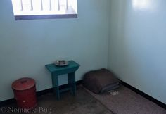 Inside of Nelson Mandela's prison cell, Robben Island, Cape Town, South Africa Nomadic Existence Nelson Mandela Prison, Prison Cell, Island Tour, Ancient Ruins, Extra Seating, Cape Town, South Africa, Places, Home Decor