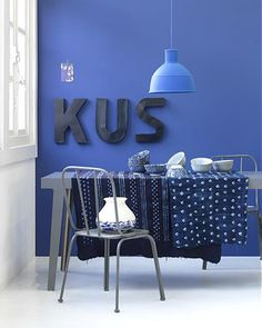 Blue wall with letters (the word 'kiss') #dining #room
