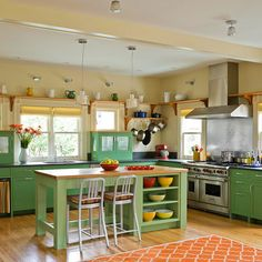 This bright, warm kitchen with open floor plan provides storage, while feels welcoming for guests and family while you prepare a meal. The pops of color on the bottom cabinets is a nice modern contrast to the warm wooden shelves and traditional molding and wood floors. The aluminum stools add a nice tie in to the stainless vent hood/backsplash.