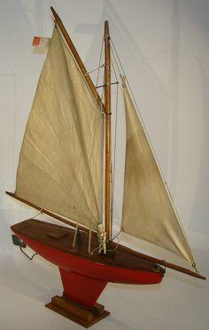 """Voilier """"Nova"""" gréement houari, foc et grand-voile aurique, avec un moteur mécanique installé dans la coque, une ouverture sur le pont, permet le passage de la clef de remontage. Le pont est vissé, pour assurer l'entretien du moteur. Le support du safran réglable, sert de protection à l'hélice tripale. Il est skippé par un marin dit Radiguet """"canotier"""". Longueur hors tout : 48cm"""