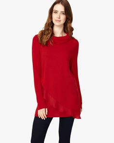 This roll neck top has a soft A-line shape for a flattering fit and features a woven and knit asymmetric layered hemline on the front with a contrast plain back and long sleeves. Wear with jeans for a stylish daytime look.
