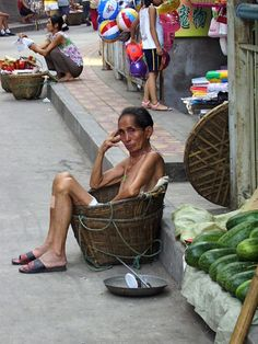 Man settled into his basket as he waits for customers needing help transporting items in Chongqing, China