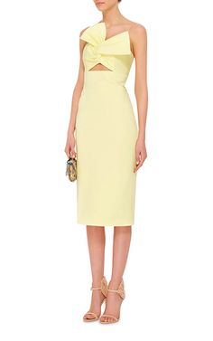 This **Cushnie et Ochs** dress features a strapless design with an architectural knot detail at the neckline, triangle cutwork detail below the knot, and a knee length pencil silhouette.