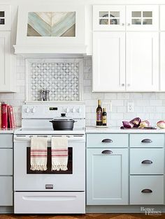 Tile can add a raised facet to a space to help boost visual interest. in this pastel kitchen, the backsplash tile -- a miniature mosaic bordered by a raised tile -- picks up on the cabinet details and offers a focal point behind the range.