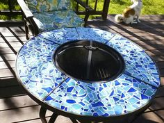My flea market flip, an old fire pit. I cut tiles to fit around, glued and grouted the glass pieces on top.