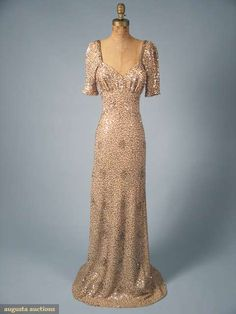 1935, Blush pink, bias cut, covered in silver and gold sequins, short sleeve, sweetheart neckline, low U-shape back.  augusta-auction.com