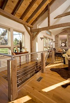This is a great example of rural modernism. You see old barn beams combined with a sleek metal look surrounding the stairwell.