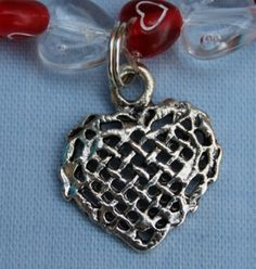 """This bracelet has red heart shaped beads with white hearts and clear transparent heart shaped beads. The metal charm has a cut out criss cross pattern. All threaded onto elastic. 17.75cm (7"""").  Materials used: Acrylic, silver coloured metal and elastic."""