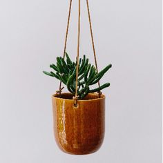 We love this dappled burnt orange ceramic hanging pot with leather ties, a perfect way to add a hint of the 70s decor to your space! Shop now on Trouva.