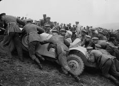 Soldiers pushing a car up a hill
