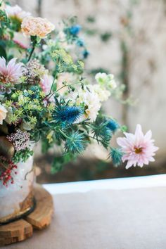 Blue thistle and pink dahlias along with dill, rice flower, pepper berries and such in a ceramic pot. Photo by Diana Marie Photography